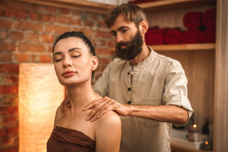 Medycyna alternatywna Terapia uzdrawiająca siedząca kobieta w ręczniku uśmiechająca się radośnie, robiąc masaż, roztrzaskając zbl obraz royalty free