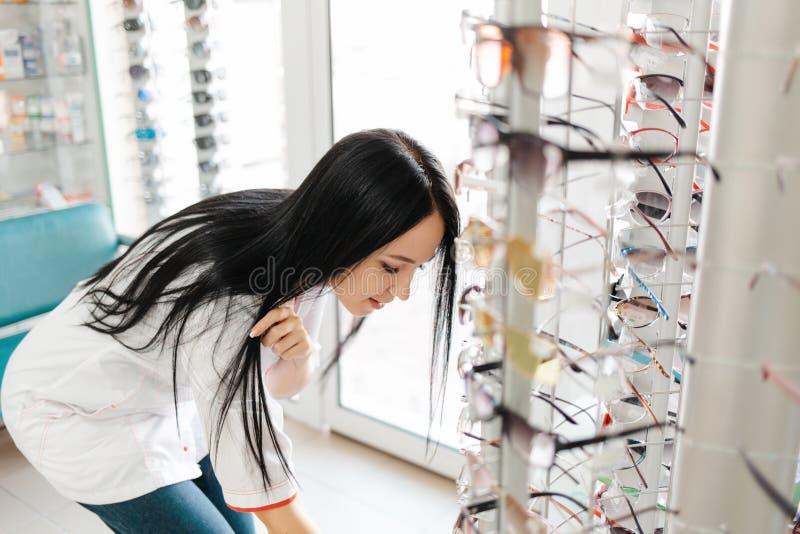 Medycyna, apteka i optyka Młoda kobieta w białym płaszczu podnosi parę okularów z okna, pochylając się ku dołowi zdjęcie royalty free