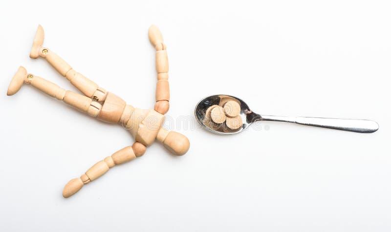 Medycyny recepta Drewniana ludzka atrapa blisko łyżkowych pełnych pigułek i pastylek Bierze medycyny pojęcie zdrowie i traktowani obraz stock