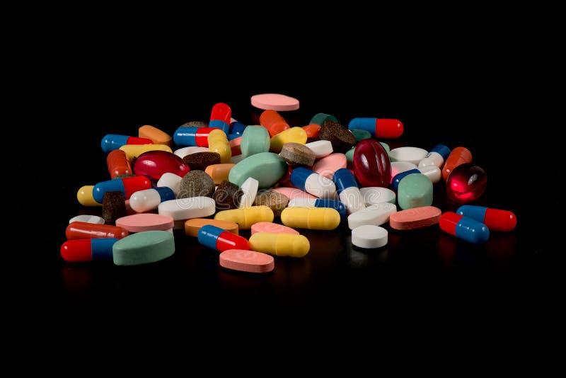 Medycyny w kapsułach wiele kolory na czarnym tle zdjęcia stock