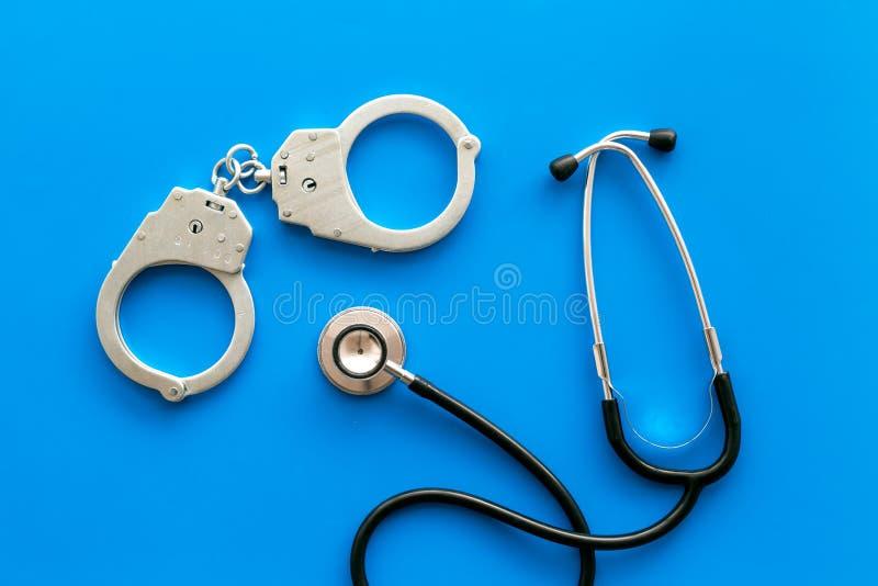 Medyczna Sprawa sądowa Areszt dla medycznego przestępstwa pojęcia Zakłada kajdanki blisko stetoskopu na błękitnego tła odgórnym w zdjęcie stock