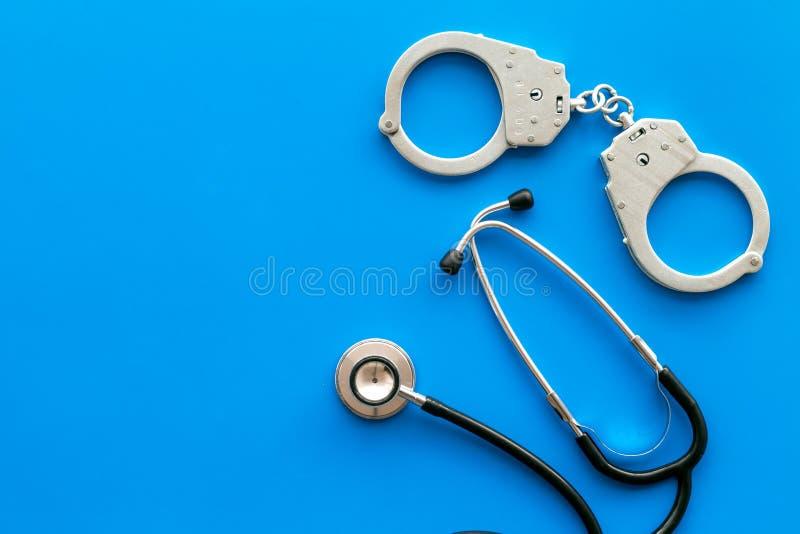 Medyczna Sprawa sądowa Areszt dla medycznego przestępstwa pojęcia Zakłada kajdanki blisko stetoskopu na błękitnej tło odgórnego w obrazy stock