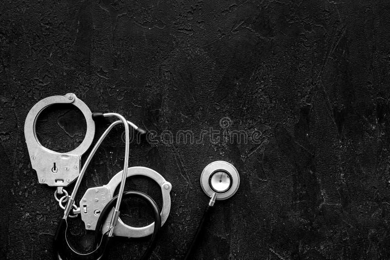 Medyczna Sprawa sądowa Areszt dla medycznego przestępstwa pojęcia Zakłada kajdanki blisko stetoskopu na czarnej tło odgórnego wid fotografia stock