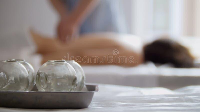 Medyczne szklane filiżanki w masażu pokoju na tle fizjoterapia obraz royalty free