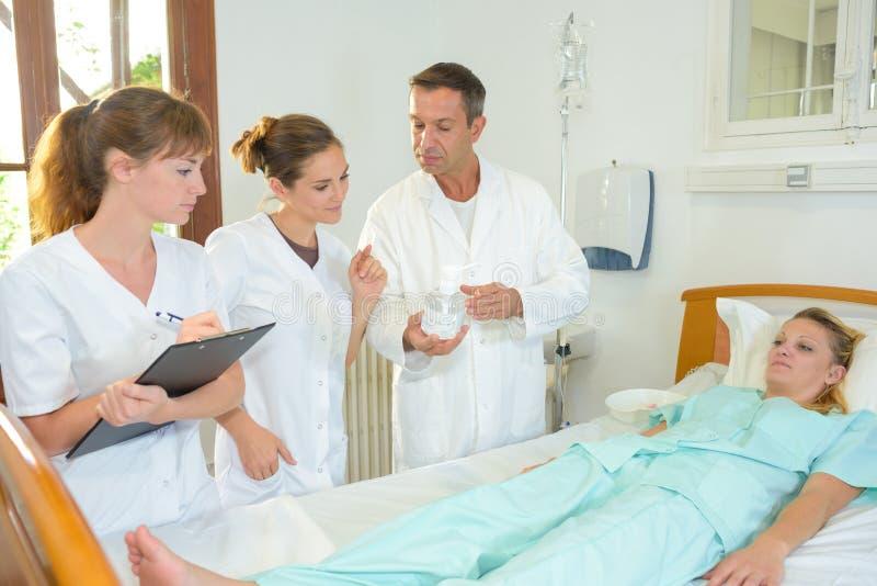 Medycznego personelu otaczający łóżkowy żeński pacjent obraz stock