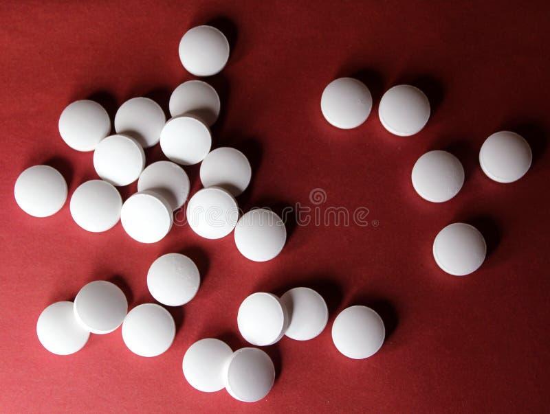 Medycznego round białe pastylki, wapń witamin zbliżenie na czerwonym tle z przestrzenią dla teksta lub wizerunek, pigu?ki zdjęcie stock