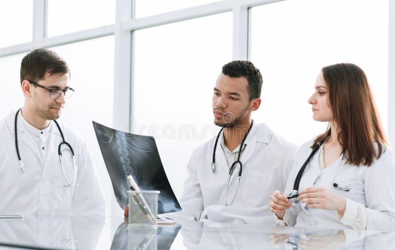 Medyczni koledzy dyskutują promieniowanie rentgenowskie, siedzi przy biuro stołem fotografia stock