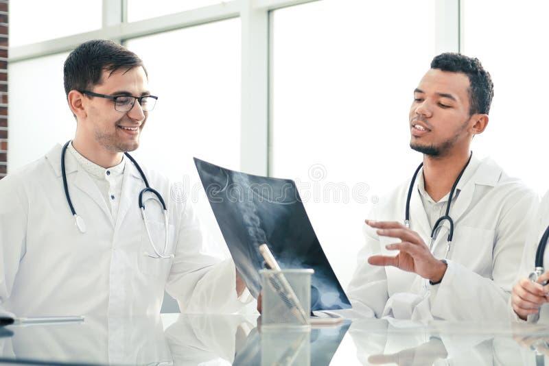 Medyczni koledzy dyskutuj? promieniowanie rentgenowskie, siedzi przy biuro sto?em obrazy stock