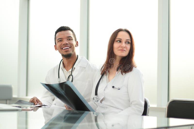 Medyczni koledzy z promieniowania rentgenowskiego obsiadaniem przy biurowym biurkiem obrazy stock