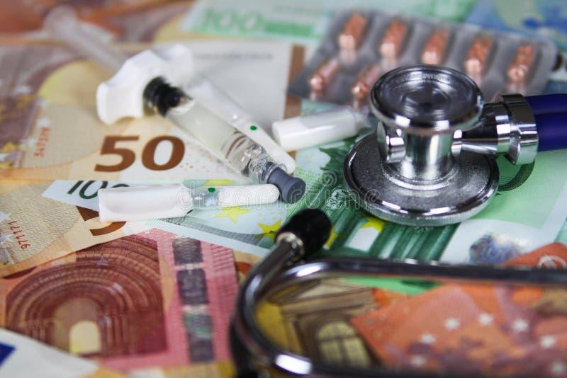 Medyczny kosztu pojęcie - stetoskop, pigułki pokrywa pęcherzami i ampules na euro papierowego pieniądze banknotach obraz stock