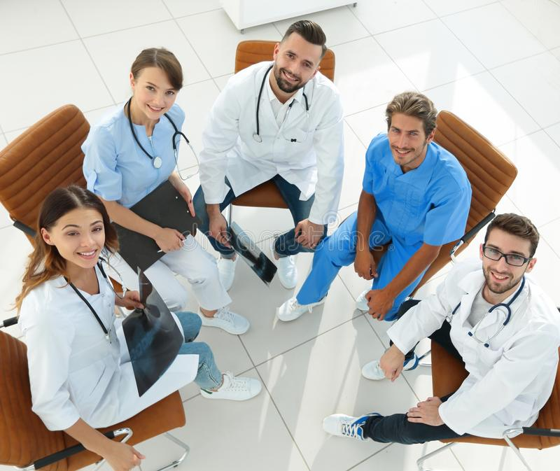 Medyczny personel dyskutuje aktualne sprawy, siedzi za biurkiem zdjęcie stock