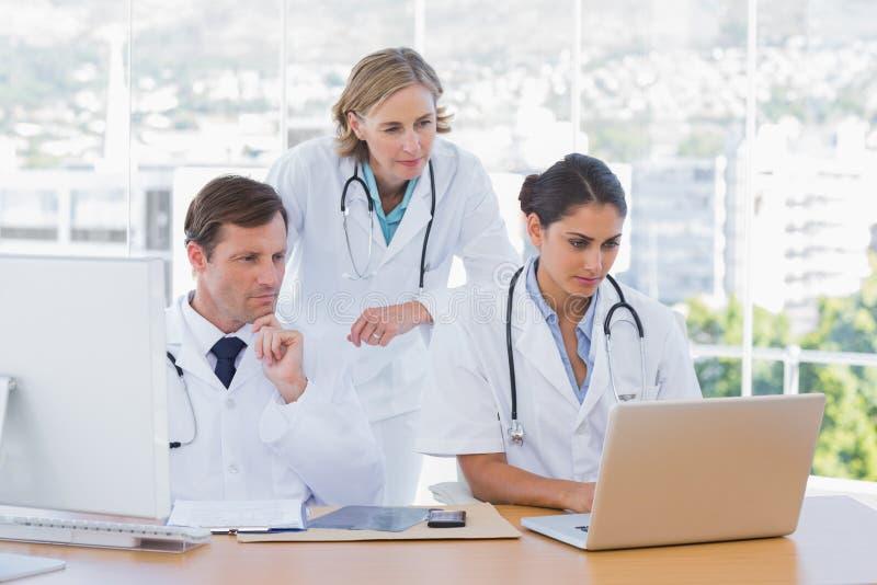Medyczny personel pracuje wpólnie na laptopie i komputerze zdjęcia royalty free