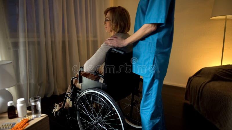 Medyczny pracownik pociesza przygnębionej starej wózek inwalidzki kobiety przy karmiącym domem zdjęcia royalty free