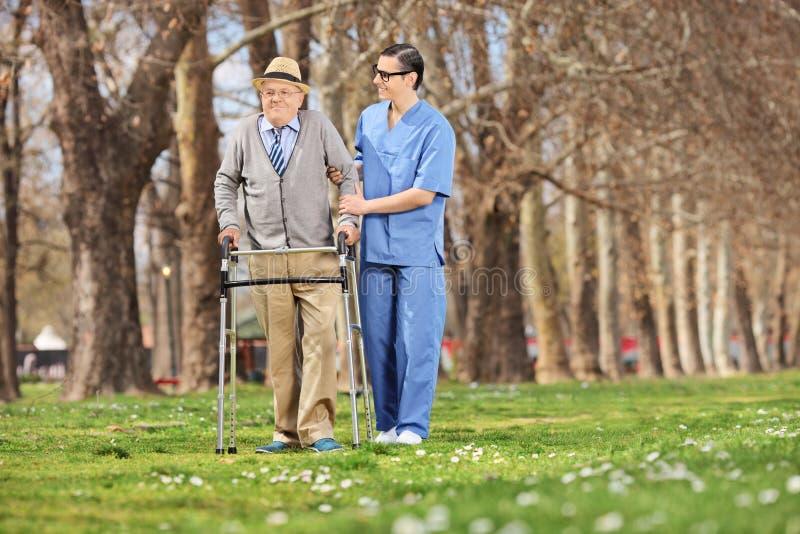 Medyczny profesjonalista pomaga seniora w parku obraz royalty free