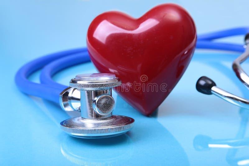 Medyczny stetoskopu i czerwieni serce na błękicie odzwierciedla tło zdjęcia stock