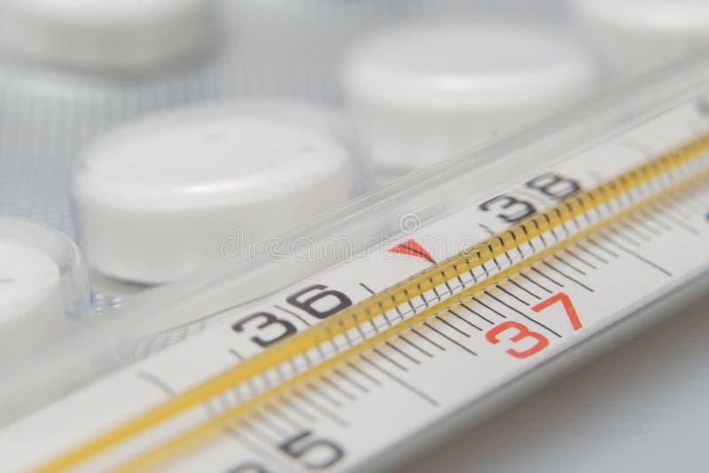 Medyczny termometr i pigułki na białym tle Medycyny i medyczny termometr zdjęcia stock