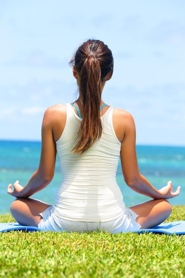 Medytaci joga kobieta na plaży medytuje oceanem zdjęcie stock