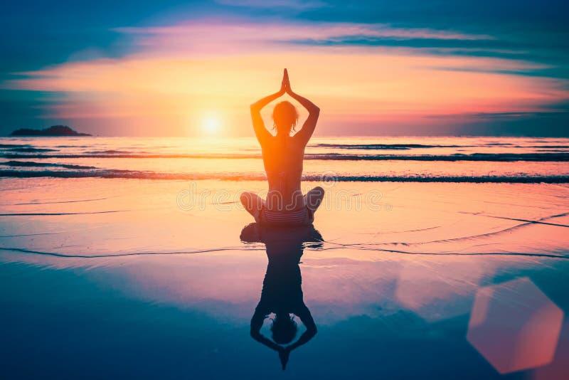 Medytaci joga kobiety sylwetka na ocean plaży fotografia stock