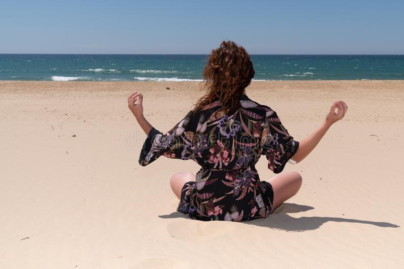 Medytacja kobiety Brunette w pozie jogi na plaży piaskowej zdjęcie stock