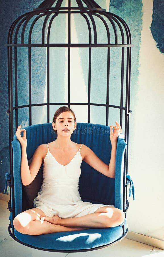 Medytacyjny i spokojny Śliczny kobieta koncentrat i medytuje w krześle Kobieta relaksuje w lotosowej pozycji w domu dosyć zdjęcie royalty free