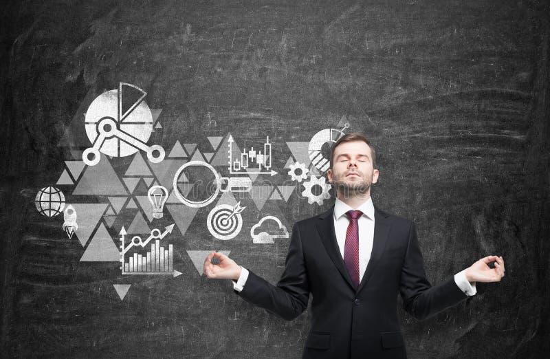 Medytacyjny mężczyzna buduje biznesowego flowchart który rysuje na czarnej ścianie behind obraz stock