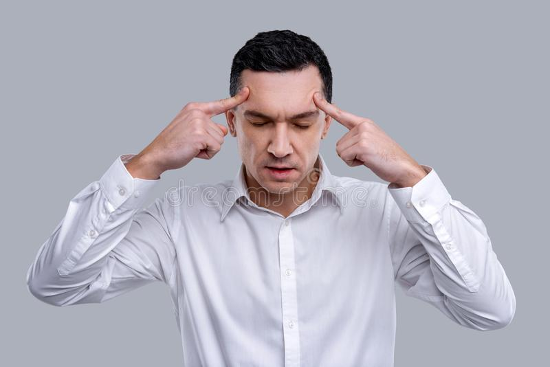 Medytacyjny mężczyzna dotyka jego świątynie podczas gdy myśleć fotografia stock