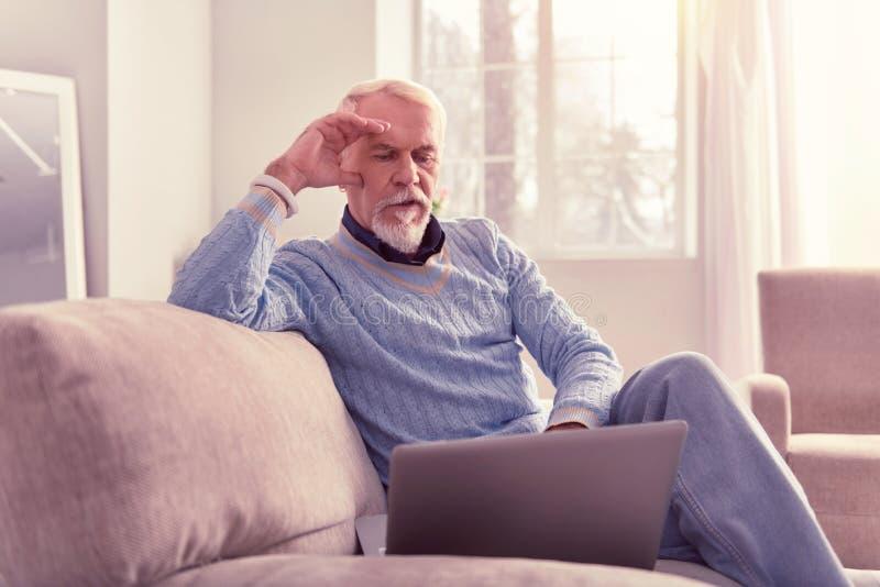 Medytacyjny stary człowiek wydaje czas z laptopem obraz stock