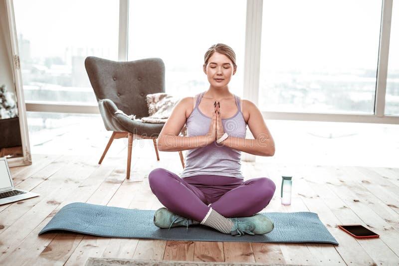 Medytacyjny zrelaksowany kobiety obsiadanie na błękit macie w lotosowej posturze obrazy stock