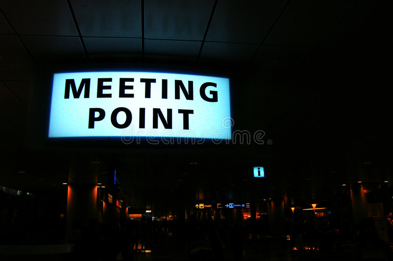 'Meeing Point' Signboard. Blue lit 'Meeting Point' signboard in a modern airport. Background show many other various signages in smaller scale. Taken at night at royalty free stock images