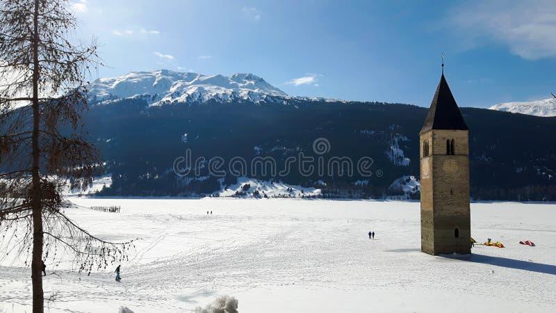 Meer in Alpen met het oude omringende ijs van de kerktoren royalty-vrije stock foto's