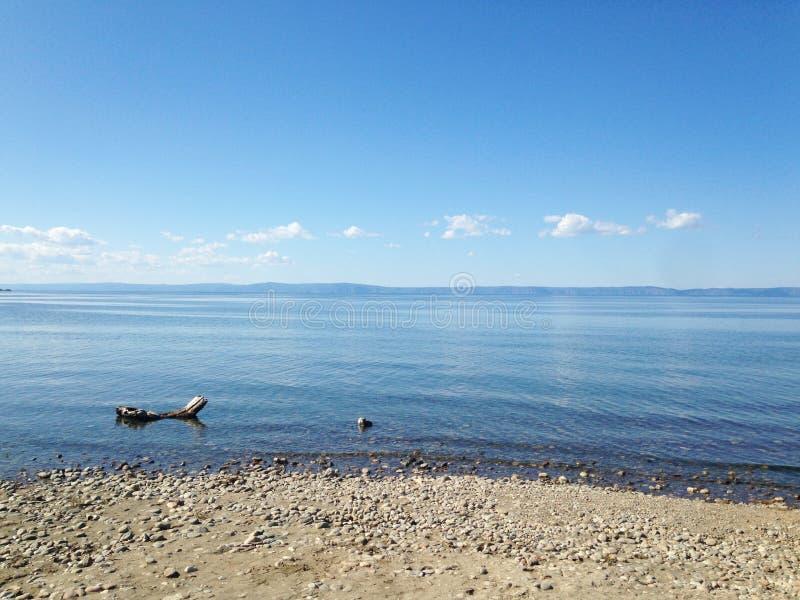 Meer Baikal, de blauwe uitgestrektheid van water en kleine stenen op de kust, een kalm landschap stock afbeeldingen