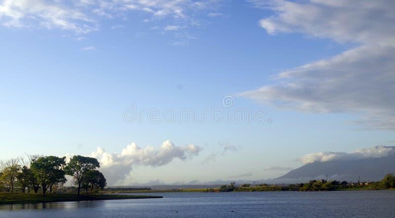 Meer, berg en bomen in een duidelijke dag royalty-vrije stock afbeelding