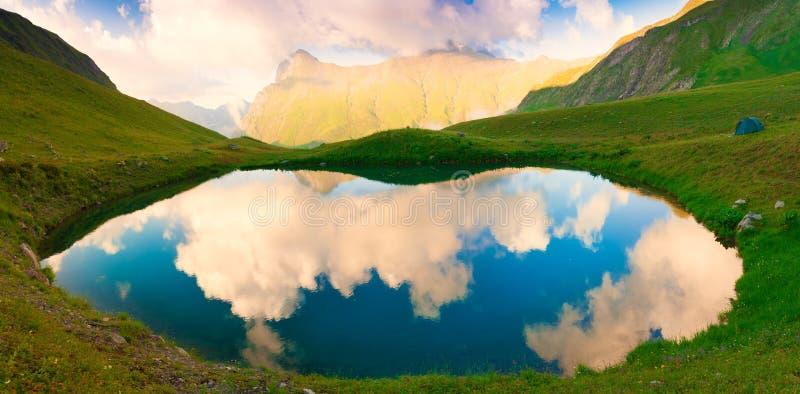Meer De bergzomer Zonsondergang Groen fantastisch gras, reflectio stock fotografie