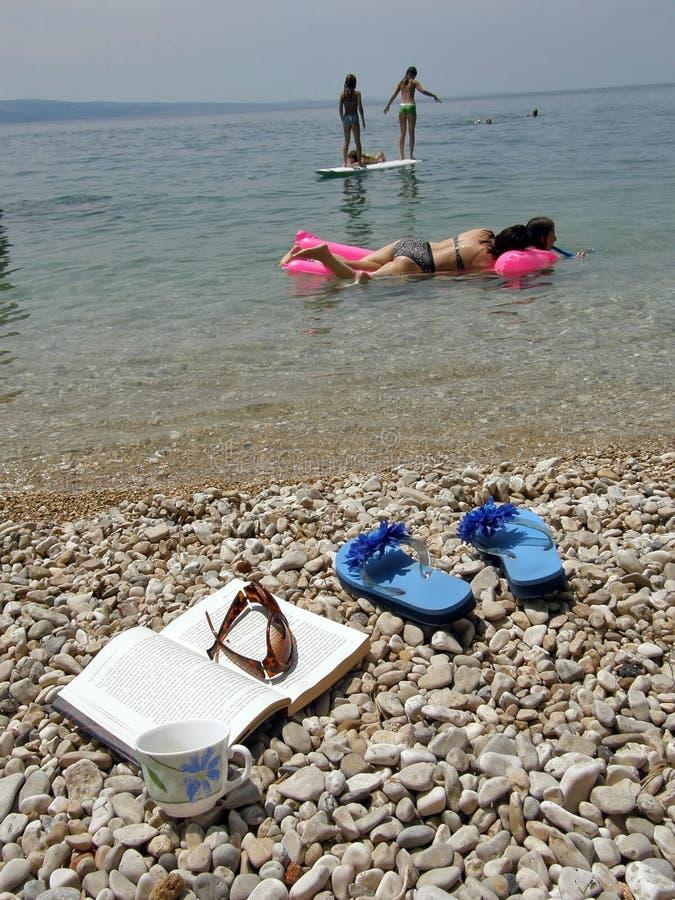 Meer, Kaffee, Buch und Familie auf Ferien lizenzfreies stockbild