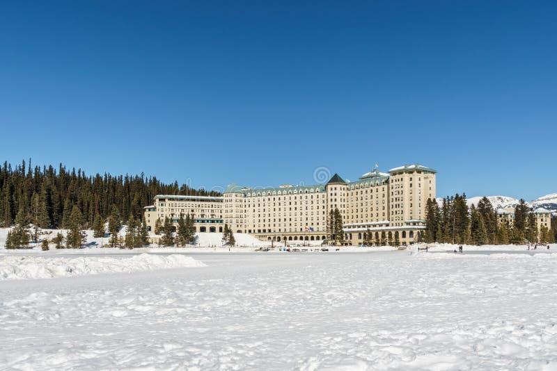 Meer Louise, CANADA - MAART 20, 2019: bevroren meer en bergen met sneeuwpieken stock foto