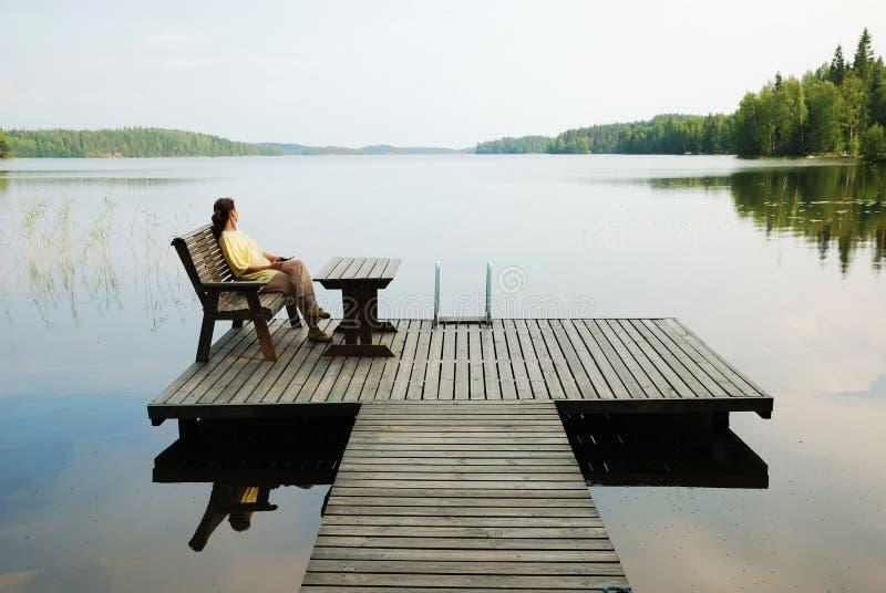 Meer met het houten platform en vrouwen rusten. stock fotografie