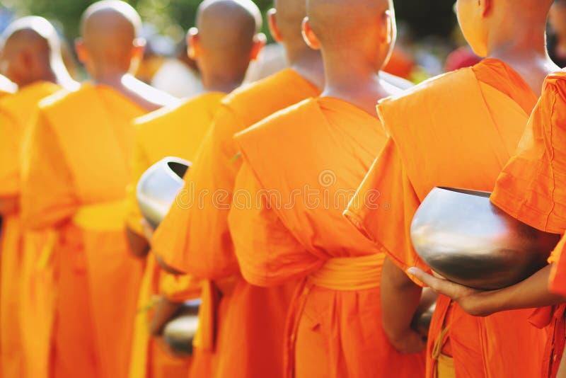 Meer monniken met geven aalmoeskom die uit het dienstenaanbod in de ochtend bij Boeddhistische tempel, de Plaats van de Cultuurer stock fotografie
