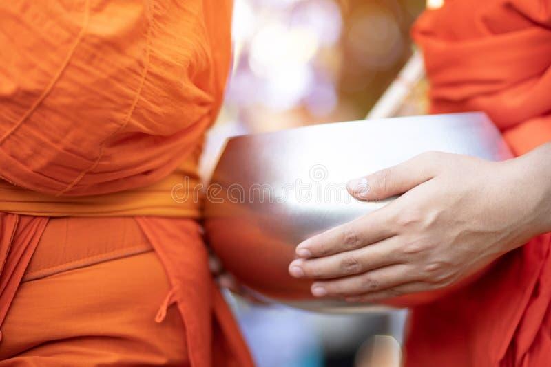 Meer monniken met handholding geven aalmoeskom die uit het dienstenaanbod in de ochtend bij Boeddhistische tempel, Si van de Cult royalty-vrije stock afbeelding
