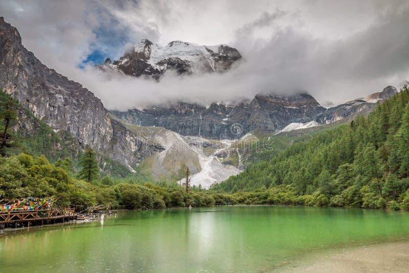Meer onder sneeuwberg in Tibet stock afbeeldingen