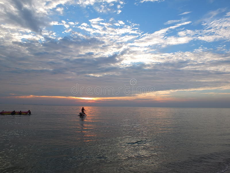 Meer an Sonnenuntergang und Himmel-Blau stockbild