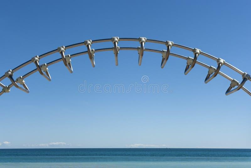 Meer und blauer Himmel mit Metallstangen lizenzfreie stockbilder