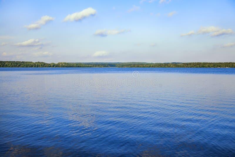 Meer van heldere blauwe kleur, hemel en bos op de kustlijn royalty-vrije stock foto's
