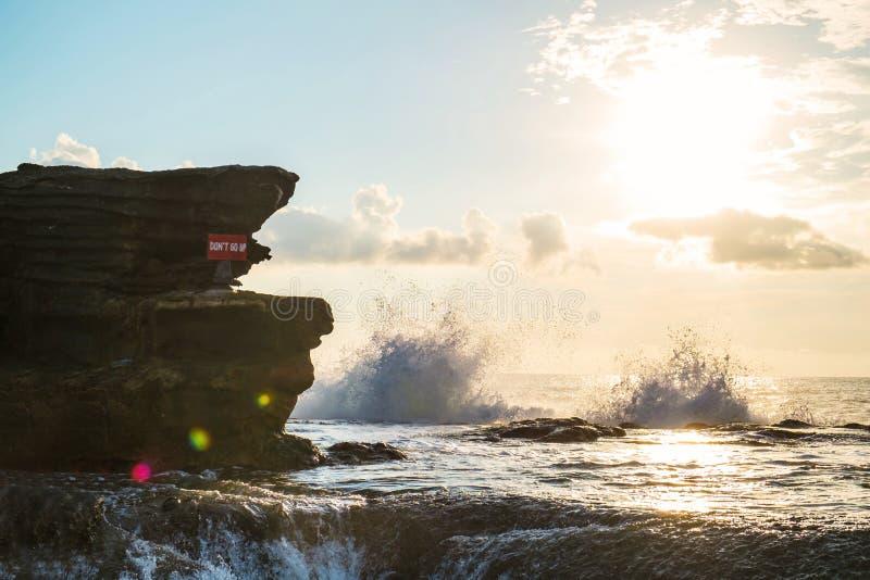 Meerblick auf der Insel mit Klippe und der Welle, die im Sonnenuntergang, mit Sonnenblendenfleckeffekt spritzt lizenzfreie stockfotografie