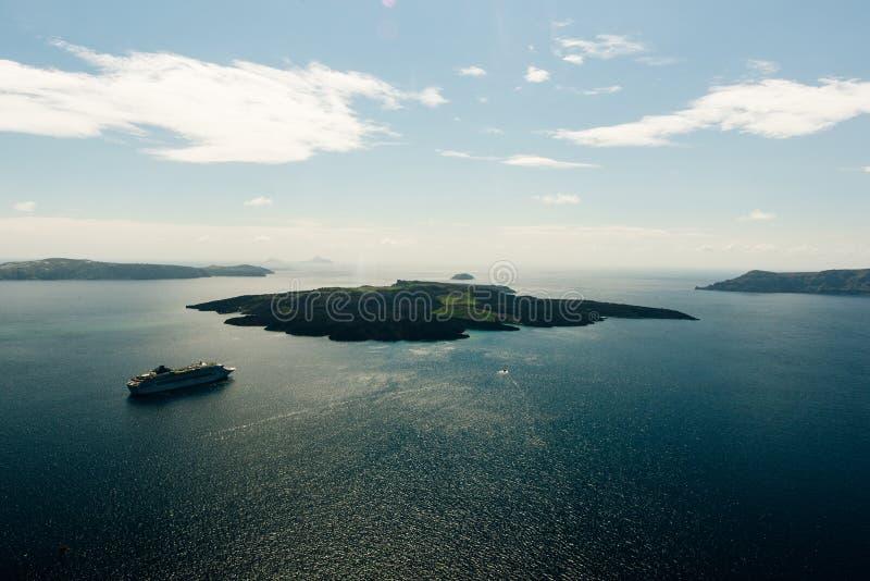 Meerblick der Insel Nea Kameni-Vulkans mit Booten und Kreuzfahrtschiffen n stockfoto