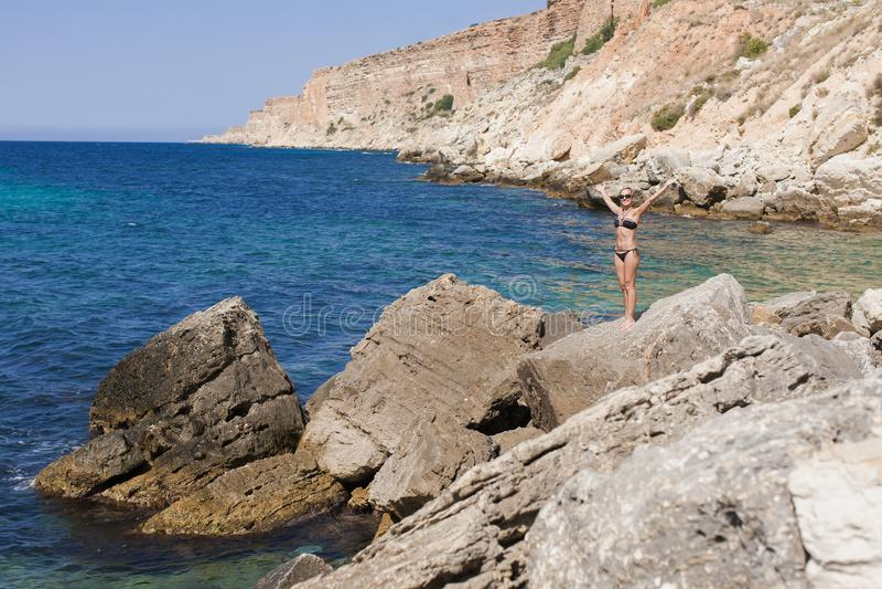 Meerblick mit kurzhaariger gebräunter blonder Frau im schwarzen Bikini lizenzfreie stockfotos