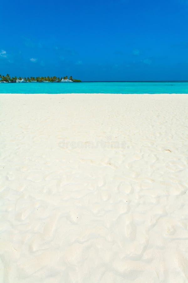 Meerblick mit Rollenwellen auf einem sandigen Strand und Booten, Malediven stockfotografie