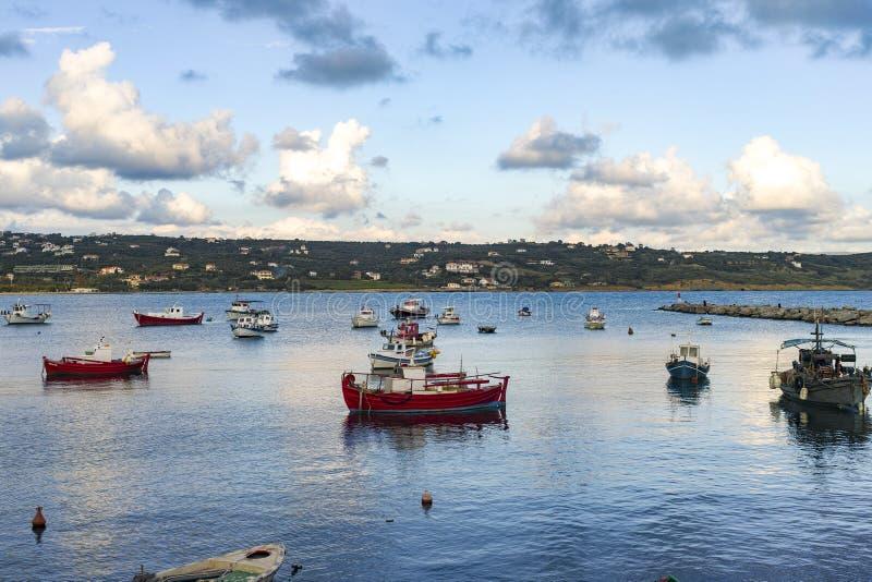 Meerblick mit Seehafen mit klarem blauem Wasser und traditionellen bunten griechischen Fischerbooten stockfotos