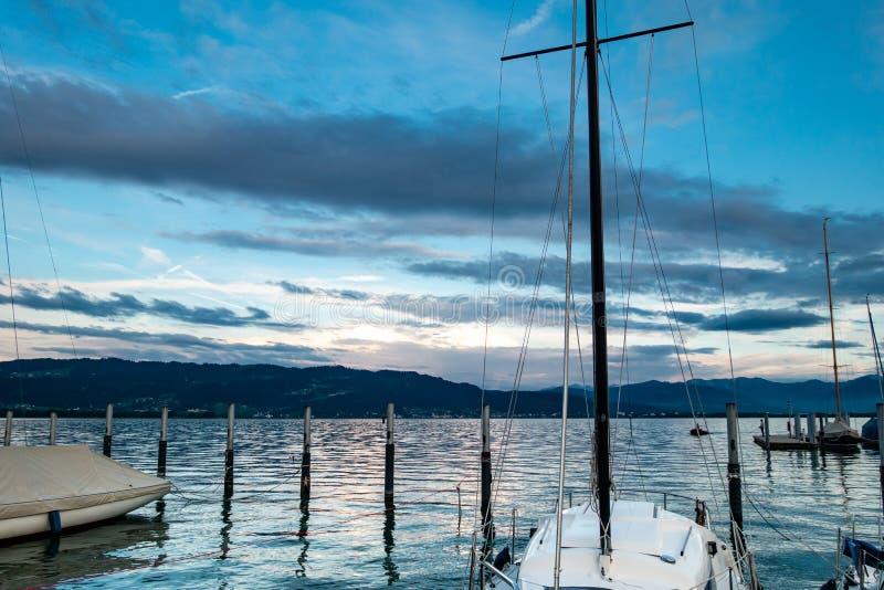 Meerblick mit Sonnenuntergang auf See Bodensee, mit Wolken, Bergen und Booten lizenzfreie stockfotos