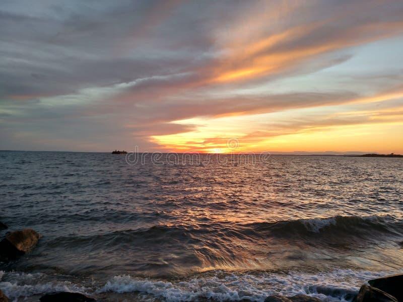 Meerblick, schöner Sonnenuntergang mit Niedrigwasserwellen stockfotos