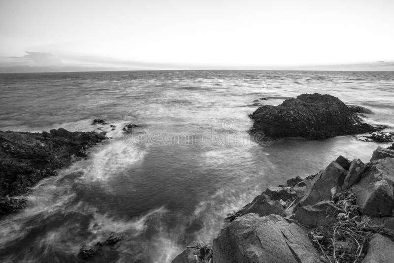 Meerblickfelsenstrand in Schwarzweiss langsame Belichtungszeit, lange Belichtung wurde verwendet, um die Bewegung zu sehen lizenzfreie stockfotografie